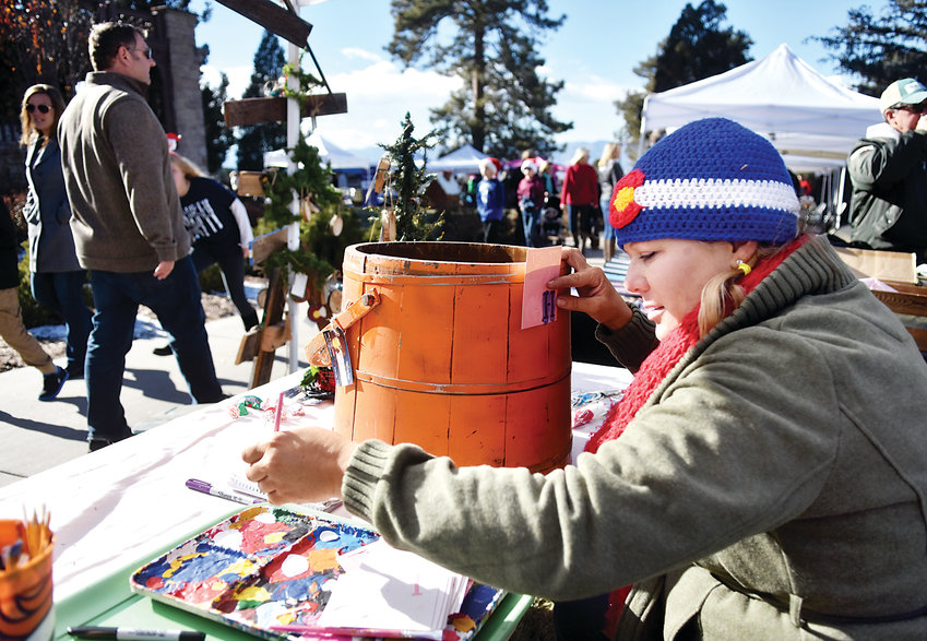 Maggie Esquibel, with Native Sons Custom Wood Design, personalizes one of her handcrafted items during the Highlands Ranch Holiday Celebration. A variety of vendors sold holiday gifts and gave away treats to visitors.