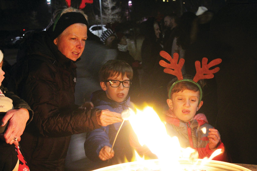 Pat Martire and her grandchildren Kamden and Luca Aldridge roast marshmallows at the annual Lone Tree tree lighting ceremony Nov. 30.