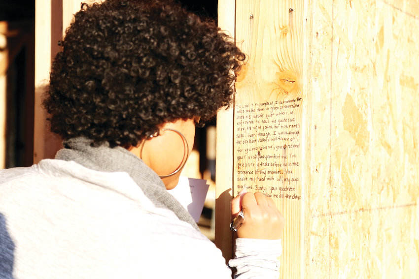 Doris Jean-Charles writes a scripture on the framing of the new Hope House resource center.