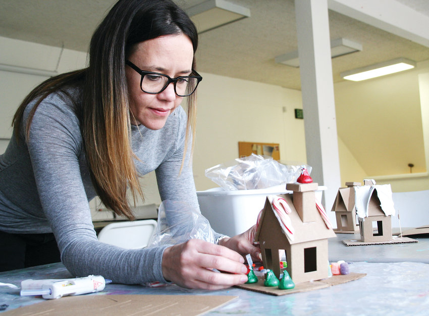 Maura McInerney, the curator of education at Foothills Art Center in Golden, puts the finishing touches on a few examples of cardboard gingerbread houses in preparation for the children's classes offered at Foothills Art Center on Dec. 8 and 15.