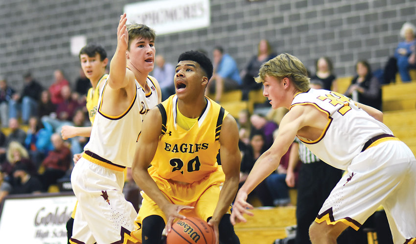 Pueblo East junior Darnell Kindred (20) is bracketed by Golden juniors Carter Thompson, left, and Kevin Mulligan during the opening round of the 11th Annual D'Evelyn/Golden Preview Classic on Nov. 29 at Golden High School.