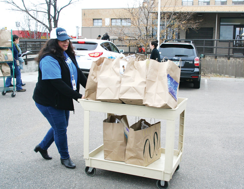 Anna Talamantez, an administrative specialist at the National Renewable Energy Laboratory (NREL), pushes a cart full of food ready to be delivered to Project Angel Heart clients in Denver on Nov. 30.