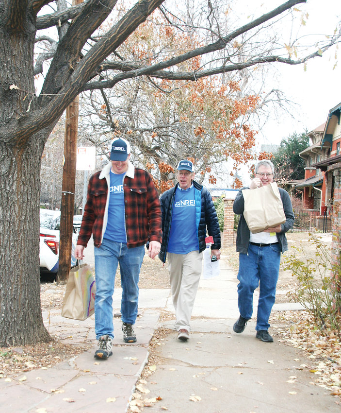 From left, National Renewable Energy Laboratory (NREL) employees Josh Martin, Ernest Tucker and Wayne Hicks make their way on a sidewalk in a central Denver neighborhood to deliver food to Project Angel Heart clients on Nov. 30.