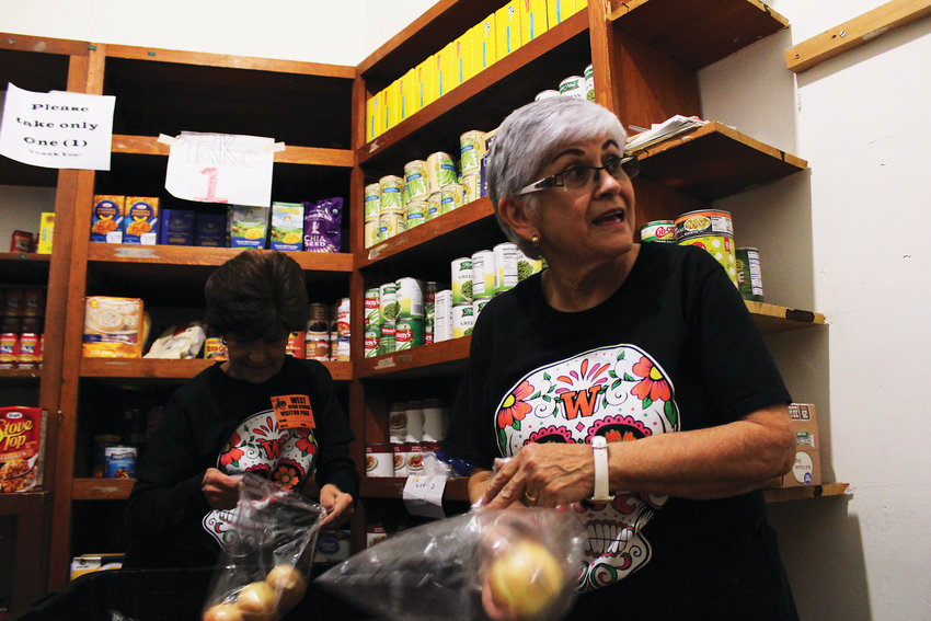Irene Jordan, left, and Mary Rita Cordova fill bags with onions for the food bank at West Leadership Academy. The pair helped open the food bank in April. It helps feeds hundreds of kids each week.