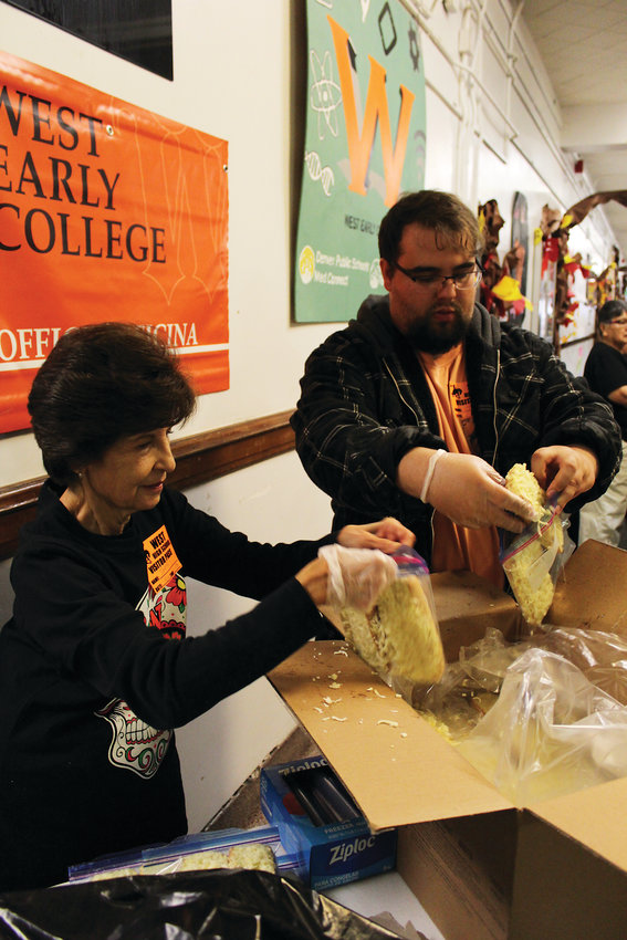 Irene Jordan, left, and her grandson Jordan Antonio help bag individual cheesy garlic bread pieces for students at West Leadership Academy. At its peak, the food bank served more than 300 students in one day.