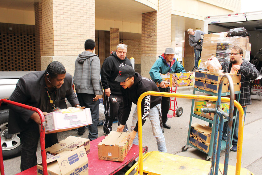 Adrien Gomez, center, drops a box of produce onto a trolley. He, as well as other West Leadership Academy and We Don't Waste volunteers, helped bring the food into the school for the food bank.