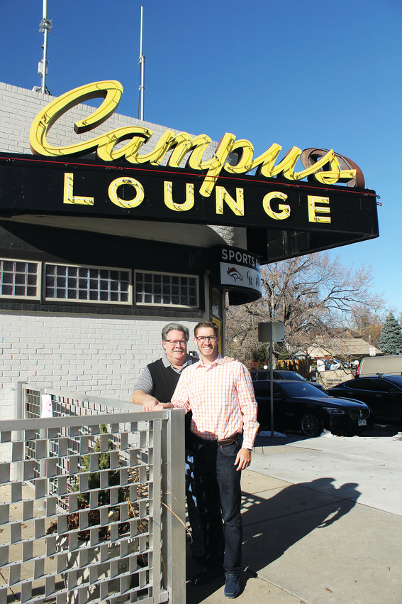 Dan and Jeff Nickless stand below the famous Campus Lounge neon sign. The father and son reopened the neighborhood bar in October.