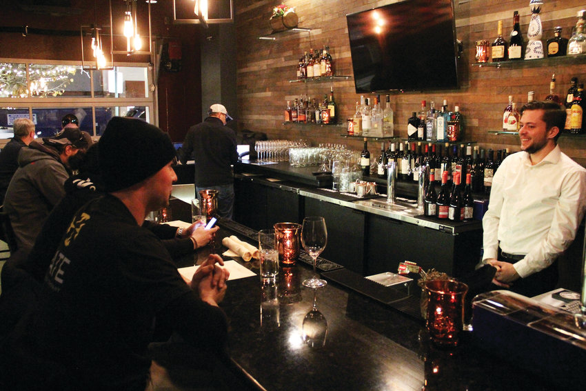 Patrons sit at the bar on opening day Dec. 4 at One Barrel, a wine bar and restaurant on the historic 3400 block of South Broadway in Englewood. The business adds a new twist to an area known for its bar scene.
