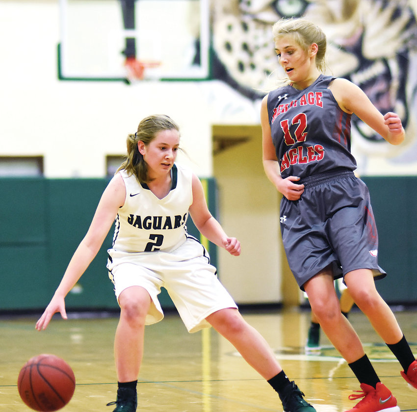 D'Evelyn junior Sydney Volheim (2) shows her ball handling skills while being guarded by Heritage senior Kylie Stephens (12) during the Jaguars' victory Dec. 5.