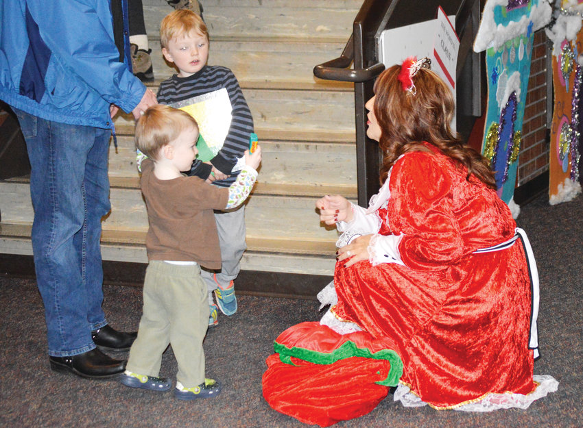 Mayor Carol Dodge, dressed as the Merry Mayor, gives candy to brothers Garrette Cindric, 5, and Declan, 2, at the city's Noel Northglenn celebration Dec. 7.