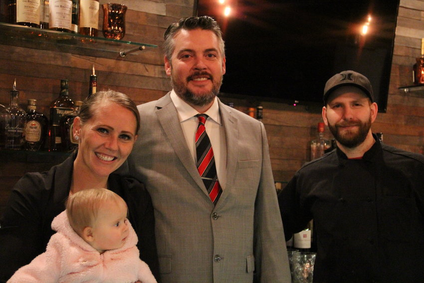 From left, Jamie Elward, 33; her husband, Jordan Blaydes, 36; and 33-year-old David Polakoff, executive chef, stand behind the bar Dec. 4 at One Barrel, a wine bar and restaurant that opened that day in Englewood. Located at 3401 S. Broadway, it's the latest in a slew of new businesses on the city's downtown block. Elward held her 6-month-old daughter, Logan Blaydes, who was along for the ride as the first customers came in.
