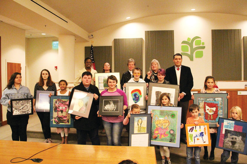 The top finalists in the City of Englewood's Student Art Contest pose with their pieces at the Dec. 3 Englewood City Council meeting. The pieces are featured in the 2019 City of Englewood calendar. In back, from left, Councilmembers Cheryl Wink, Amy Martinez, Rita Russell, Laurett Barrentine and Dave Cuesta stand with the group.
