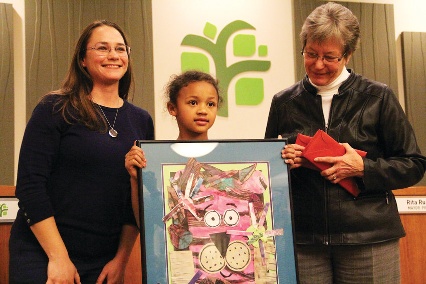 "Talia Green, a student at Clayton Elementary School, holds up her piece, ""Striped in Pink,"" at a ceremony to recognize student artists at the Englewood City Council meeting Dec. 3. The artists' work was featured in the 2019 City of Englewood calendar. Green is flanked by Councilmember Amy Martinez, left, and Mayor Pro Tem Rita Russell."