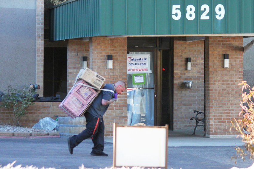 A mover hauls a load out of the Windermere apartment tower on Dec. 15.