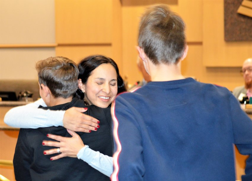 Newly appointed Westminster City Councilor Sheela Mahnke hugs her son Ryman, 12, while son Gibson, 14 looks on at the end of the Westminster Council meeting Dec. 17.