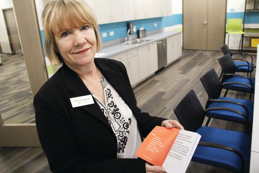 Linda Larkin, art therapist at Alumia Institute, holds up on Dec. 18 a book of easy-to-read advice and insights — based on research — for people or families who have received a dementia diagnosis. Alumia is a therapy campus for those in the early stages of dementia, located at 9800 E. Geddes Ave.