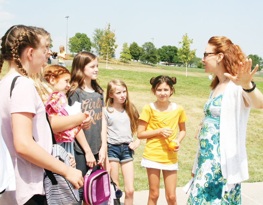 Bell Middle School Principal Michele DeAndrea-Austin, far right, asks a group of sixth-grade girls about how the first day of school was going for them during the students' lunch period on Aug. 16. This year, about 970 students are enrolled at Bell, and about 775 of them are sixth and seventh graders. This year, because of the district-wide sixth-grade shift, at least half of Bell's enrollment are new to the middle school.