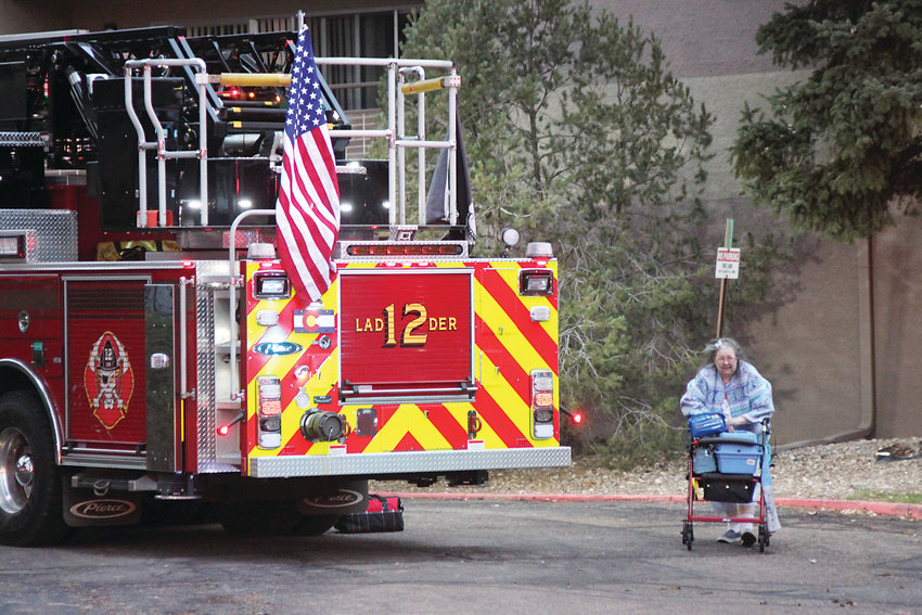 A woman makes her way out of the Windermere apartments in Littleton on Nov. 17 after a first-floor fire sent residents fleeing. One man died and at least 12 people were injured.