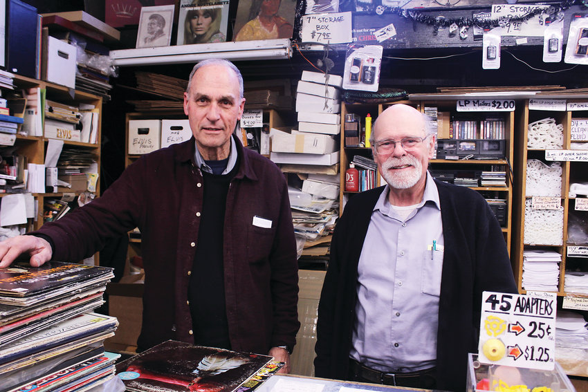 "Dave Stidman, left, and Duane Davis stand behind the counter at Wax Trax in Capitol Hill. Stidman said that their love of music has kept them like ""perpetual teenagers."""