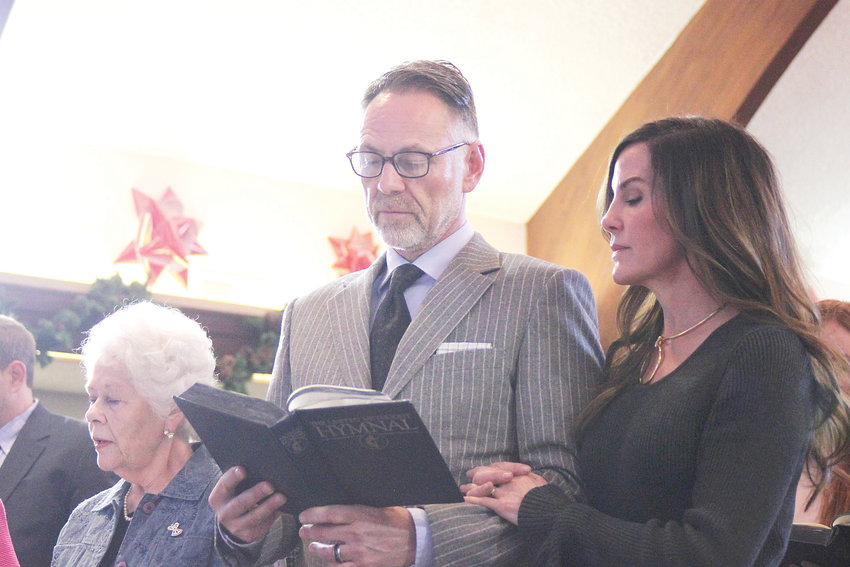 "From left, Garrett Ray's widow Nina, son Ben and daughter-in-law Lynne sing the hymn ""Morning has Broken"" at Ray's funeral at Columbine United Church on Dec. 30."