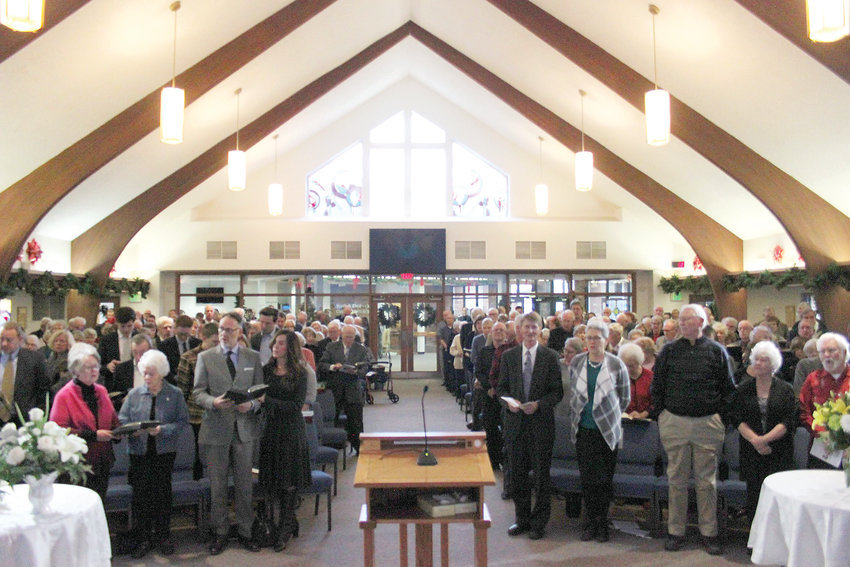 "Mourners stand to sing the hymn ""Morning is Broken"" during the funeral of former Littleton Independent editor Garrett Ray at Columbine United Church on Dec. 30."