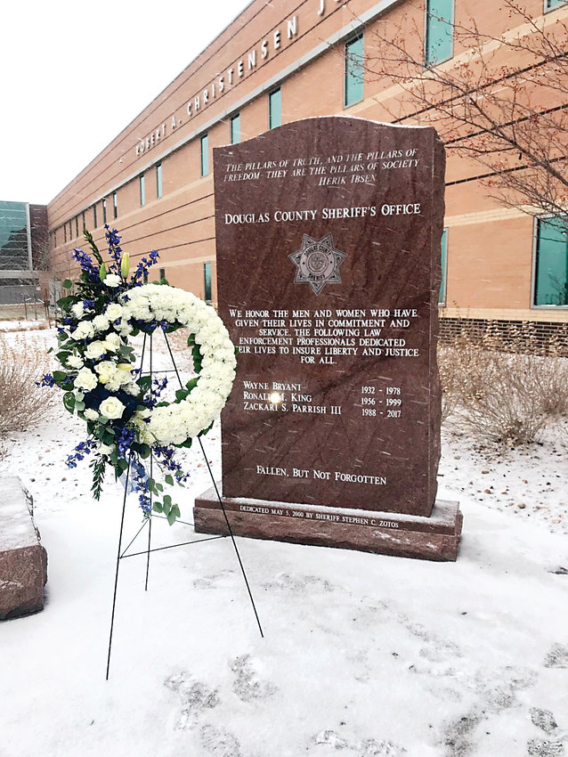 A wreath next to a monument for fallen officers honors the life and service of Deputy Zackari Parrish outside the Douglas County Justice Center in Castle Rock.