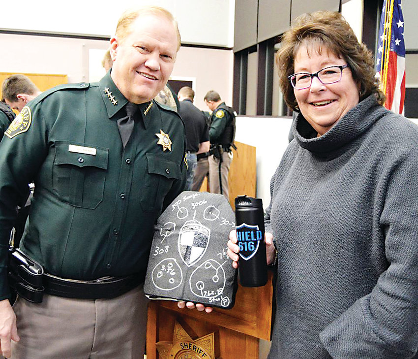 Jefferson County Sheriff Jeff Shrader, left, talks with Carla Seelinger of Conifer on Dec. 27 following a SHIELD616 presentation when 19 sheriff's deputies and officers with the Lakeside, Edgewater and Mountain View police departments received specialized tactical gear. Seelinger is one of the many supporters who made the donation possible.