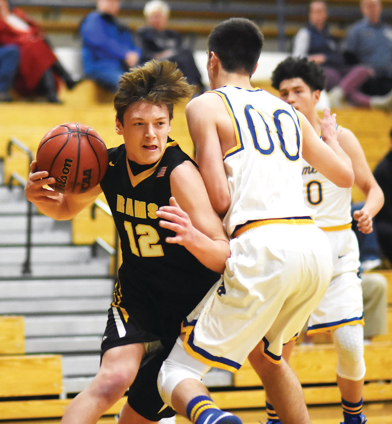 Green Mountain junior Trey Towndrow (12) drives around Wheat Ridge junior Dominic Bronk (00) during the Class 4A Jeffco League opener for both the Rams and Farmers on Thursday, Jan. 3. Wheat Ridge took a 62-56 victory.