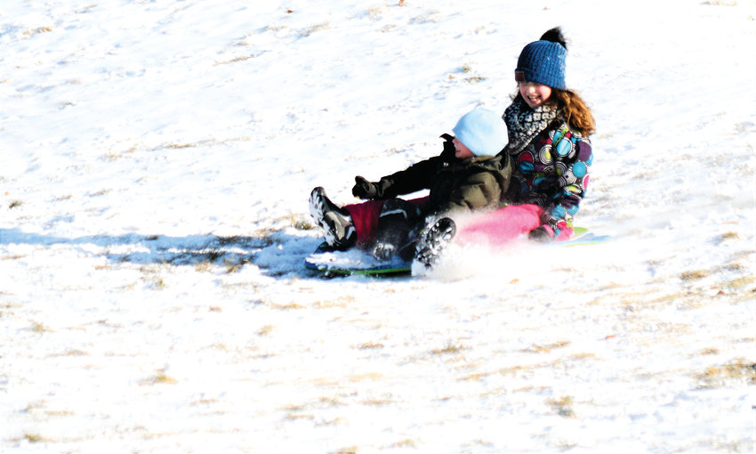 Maya Steinbecker, 10, guides her brother Bahn, 4, down the hill at Westminster's Cotton Creek Park Jan. 1.