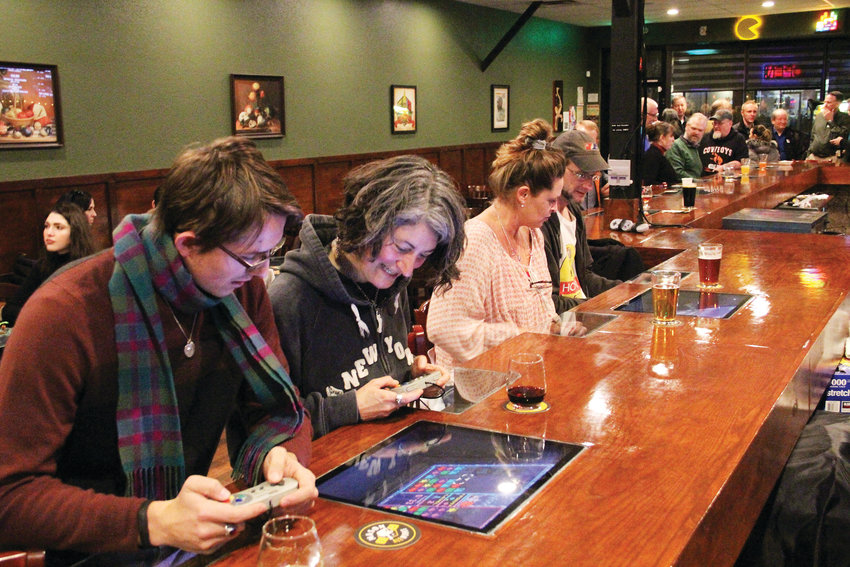 Tristen Kocher, 22, left, and Essie Rose, 48 — a regular at the bar, from Denver — play an arcade game Jan. 15 on a screen built into the bar at The Tabletop Tap. The bar at 3394 S. Broadway in the downtown Englewood area also offers more than 130 board games.