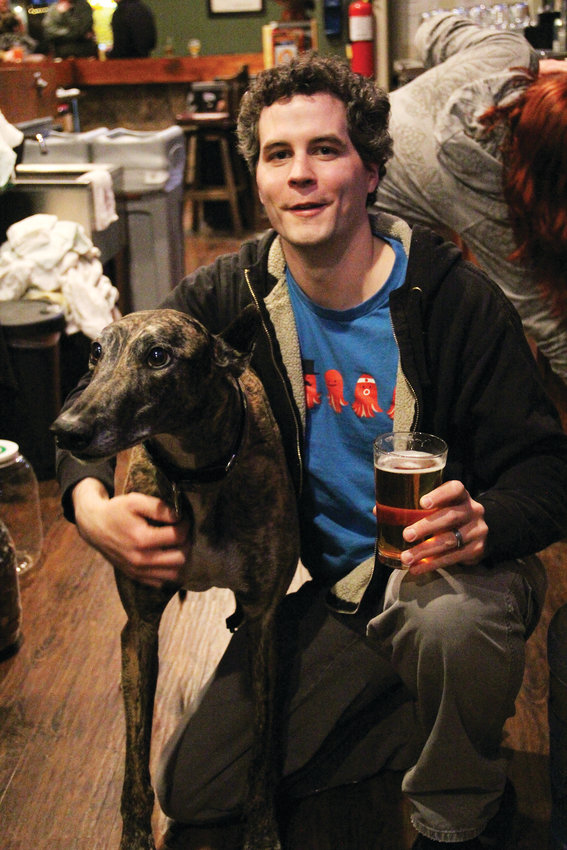 "Jason Ungate, 32, kneels next to his dog, Guybrush, Jan. 15 at The Tabletop Tap bar in Englewood. The owners of the bar are Ungate and his wife, Kristin. ""And our greyhound,"" Ungate jokes."