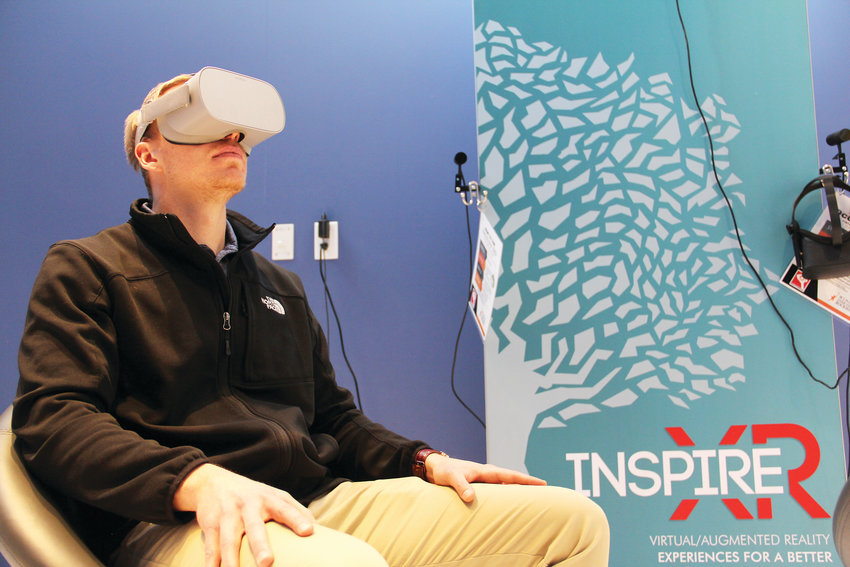 Ben Theune, spokesman for Wings Over the Rockies, uses a virtual-reality headset Jan. 17 that shows visitors what it's like to fly a plane. That virtual content at the Boeing Blue Sky Aviation Gallery is created by Reality Garage in Boulder.