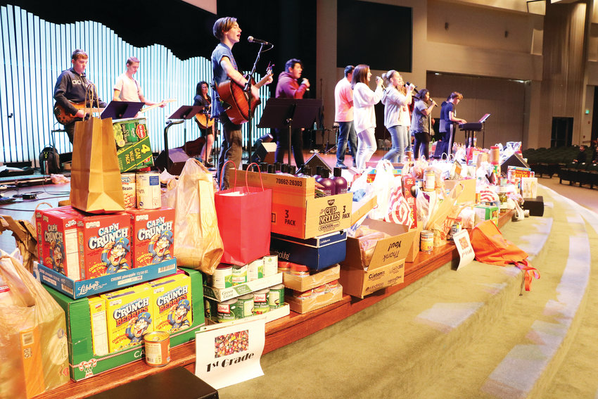 The Faith Christian Academy chapel in Arvada had piles of food stacked along the edge of the stage on Jan. 23, as kindergarteners through eighth graders who attend the school brought in food to donate to area charity Community Table (formerly known as the Arvada Food Bank).