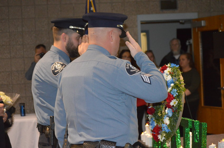 Members of the Adams County Sheriff's Department honor guard salute a wreath honoring slain deputy Heath Gumm at a vigil in his honor Jan. 24 -- the one year anniversary of his death.