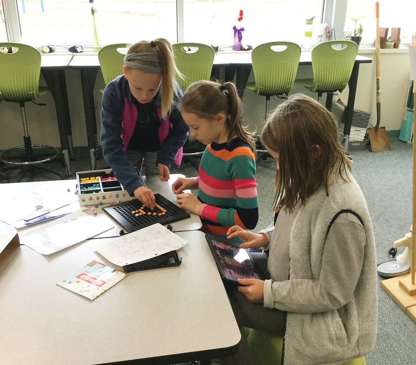 Three Fairmount Elementary School fifth graders, from left clockwise, Hadley Nauslar, Sally Kohara and Kaasen Pass, on Oct. 9, 2018, use the Bloxels platform to design and code a digital game for their younger study buddies to play to learn about being safe and smart on the internet.