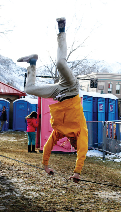 Harry Bruno, a freshman studying materials and metallurgical engineering at the Colorado School of Mines, performs a cartwheel on a slackline at the fifth annual UllrGrass Music & Beer Festival on Jan. 26 at Parfet Park in downtown Golden.