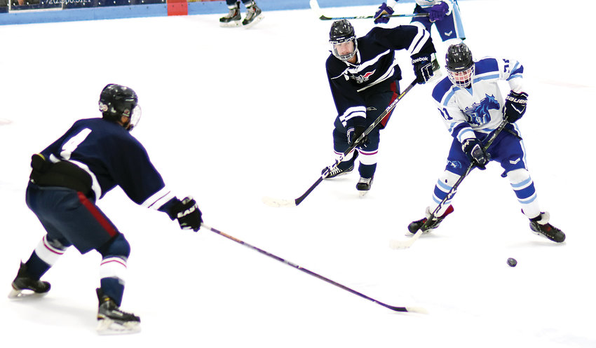 Ralston Valley forward Cameron Pietrasiewicz (91) controls the puck in the neutral zone as a pair of Dakota Ridge players close in Jan. 22 at Apex Ice Arena. The Mustangs suffered a 4-2 loss to the Eagles.
