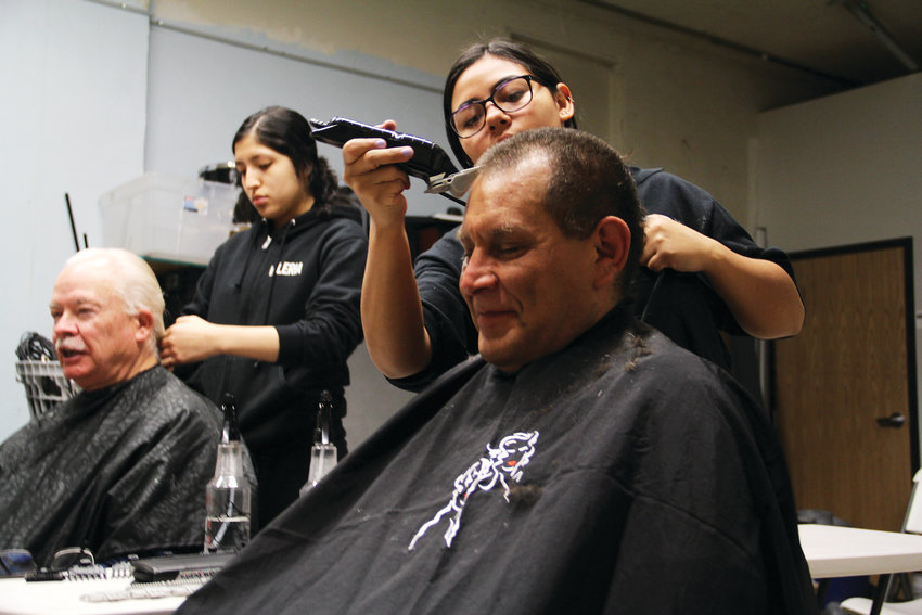 "Ron Aragon, 53, front right, smiles as he gets his hair cut on Jan. 29 by Lizzy Hernandez, 17, a cosmetology student at Colorado's Finest High School of Choice in Englewood. Hernandez and Valeria Guerra, 17, also a Finest cosmetology student, gave haircuts to the homeless at Giving Heart homeless-services center as part of a ""magnet"" event to help draw homeless people to take the annual Point-in-Time survey administered by volunteers with the Metro Denver Homeless Initiative. It's difficult to get a haircut while on the streets, Aragon said. ""This is a godsend right now."""