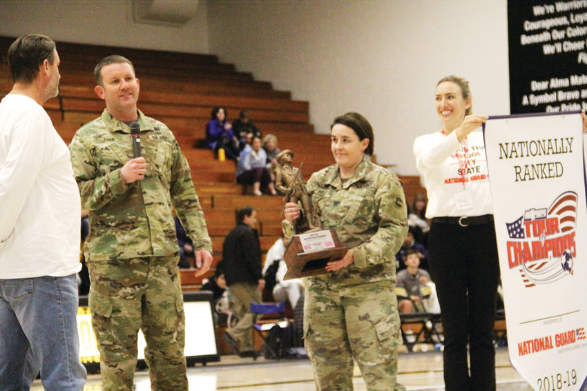 Personnel from the Colorado Army National Guard presented head coach Mark Hampshire and the Arapahoe varsity soccer team Jan. 30 with the Tour of Champions accolade at an Arapahoe boys varsity basketball game's halftime.