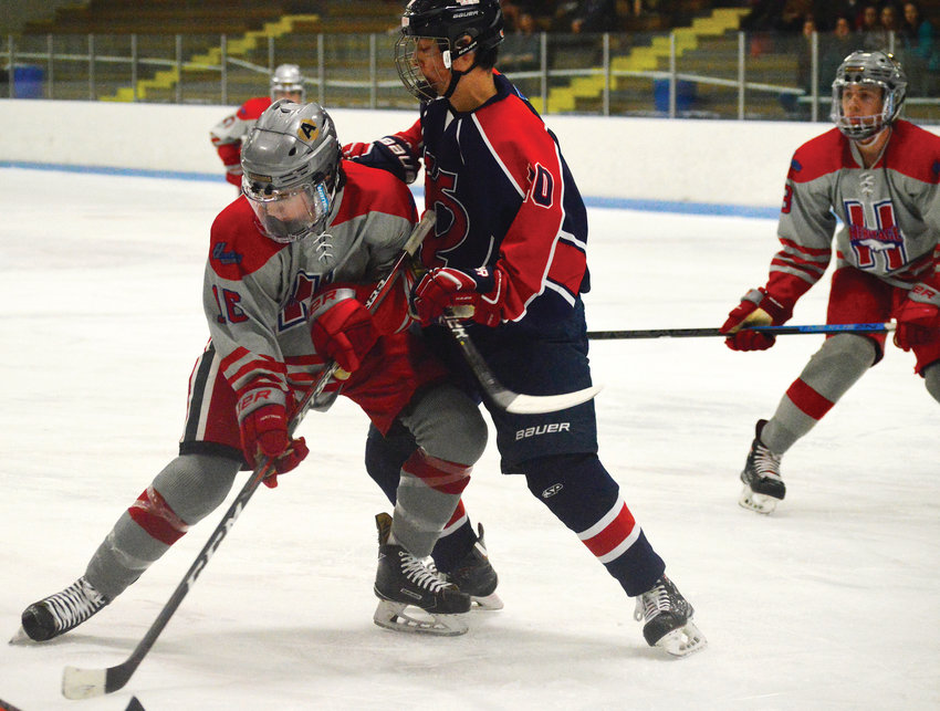 Heritage's Patrick Burke (left) and Kent Denver's Will Kandel attempt to control the puck following a faceoff in the Feb. 2 game at the South Suburban Ice Arena. Burke had an assist in Heritage's 3-2 victory.