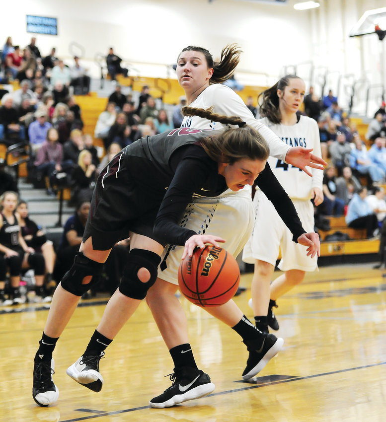 Horizon's Samantha Deem is fouled by Mountain Range's Allie Brich, during 2nd quarter action of the Feb. 1 game at Mountain Range High School in Westminster. The Hawks easily defeated the Mustangs, 70-21.