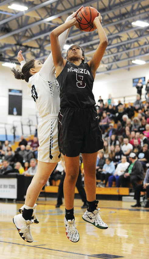 Horizon senior forward Caleese Ramirez attempts a shot against Mountain Range's Anna Giampietro, during first quarter action Feb. 1, at Mountain Range High School in Westminster.  The Hawks cruised to an easy 70-21 Front Range League win.