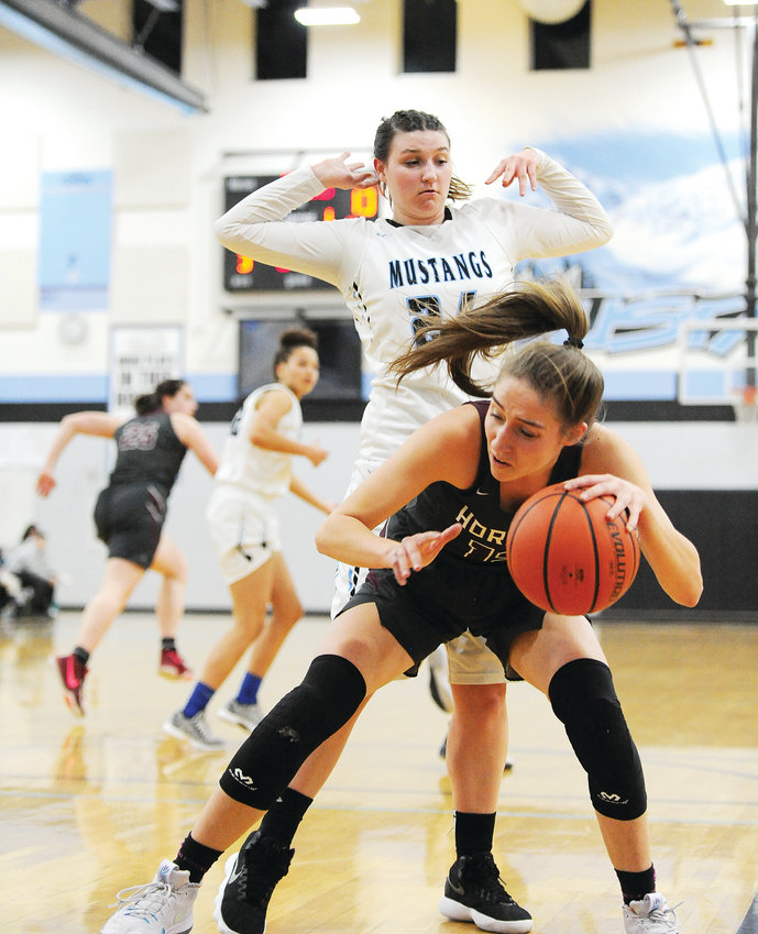 Horizon's Aly Jimenez tries to control the ball, despite defensive pressure from Mountain Range's Allie Brich, during the 2nd quarter of a Feb. 1 game at Mountain Range High School in Westminster. The Hawks won easily, 70-21.