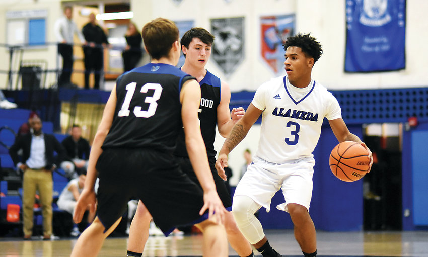 Alameda senior Isiah Lawson (3) attempts to break free of a double-team Jan. 29 against Englewood. Alameda took a 57-49 victory, but a close loss to Conifer on Feb. 1 might very well close Alameda its first boys basketball league title in nearly two decades.
