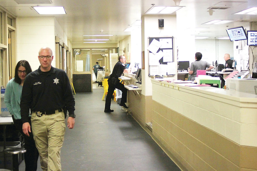 Arapahoe County Bureau Chief Vince Line, left, walks through the booking area of Arapahoe County's jail on Feb. 7. Inmates being booked in or released from the jail are brought through this area in close proximity, Line said.
