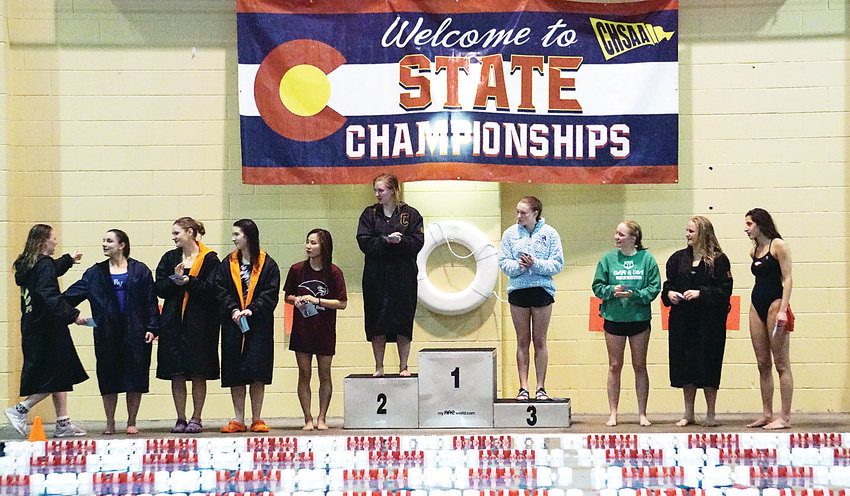 Ralston Valley senior Tori Sayers, second from the left, greets Arapahoe senior and state diving champion Franny Cable as divers take the podium. Sayers placed 10th and Ralston Valley sophomore Izzy Gregersen, third place on podium, medaled during diving competition at the Class 5A girls swimming state meet Saturday, Feb. 9, at VMAC in Thornton. Ralston Valley junior Payton Roberts placed 12th.