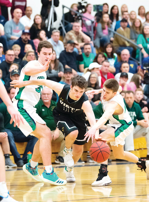 Mountain Vista's Ben Grusing squeezes through ThunderRidge defenders Bailey Verk, left, and Colton Sanders. Vista staged a late-game comeback and won on a last-second three-pointer 53-52 on Feb. 15.