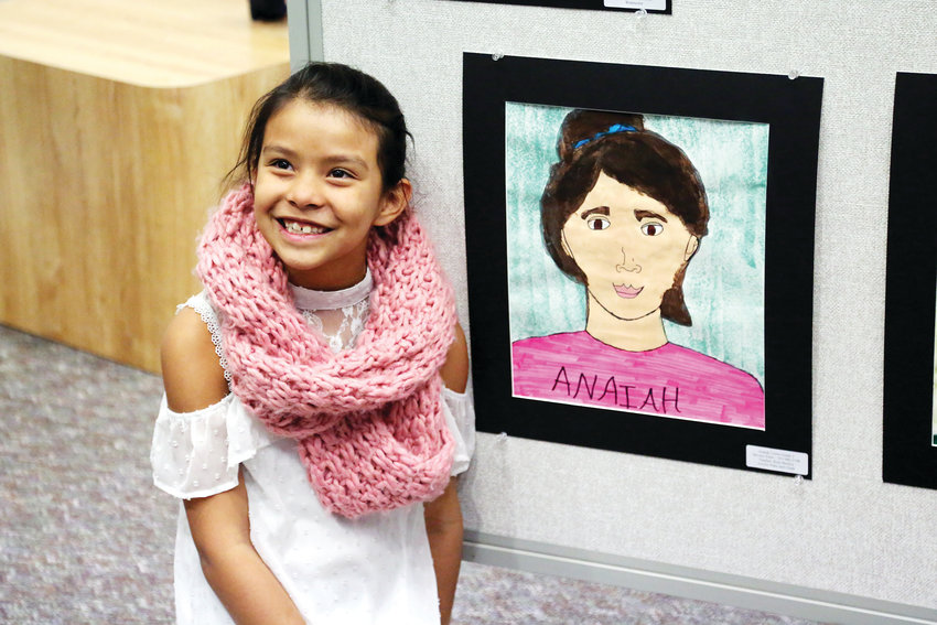 Anaiah Cortes, student at Stevens Elementary, poses for a picture next to her self-portrait.
