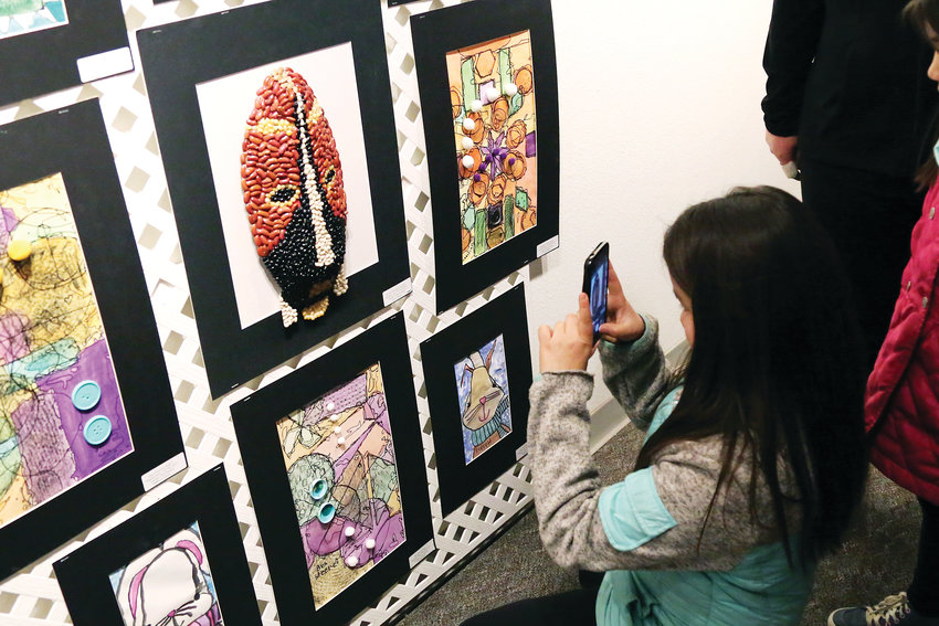 Korryn Domgaard, fourth-grader at Mitchell Elementary, takes a picture of her mixed media art on display at the Elementary Jeffco Schools Foundation Art Exhibit.