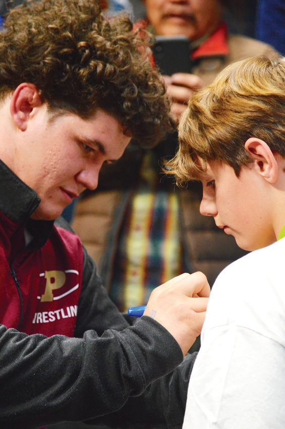 Ponderosa's Cohlton Schultz signs the shirt of a young fan.